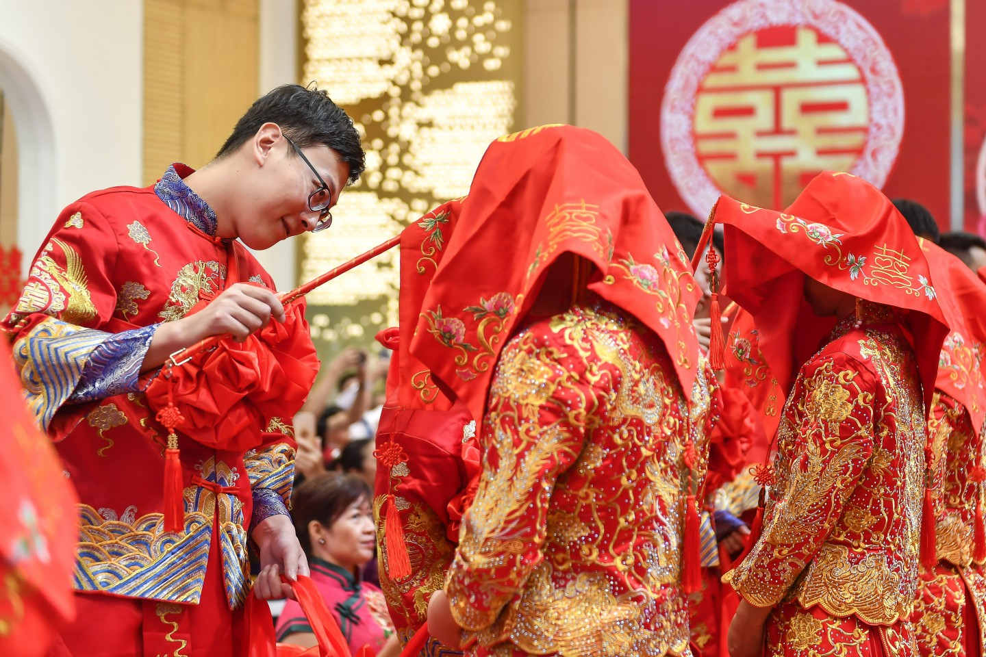30 couples tie the knot on 11 November 2019 at Guangzhou, wearing traditional Chinese wedding gowns. The picture shows the groom unveiling his bride. (CNS)