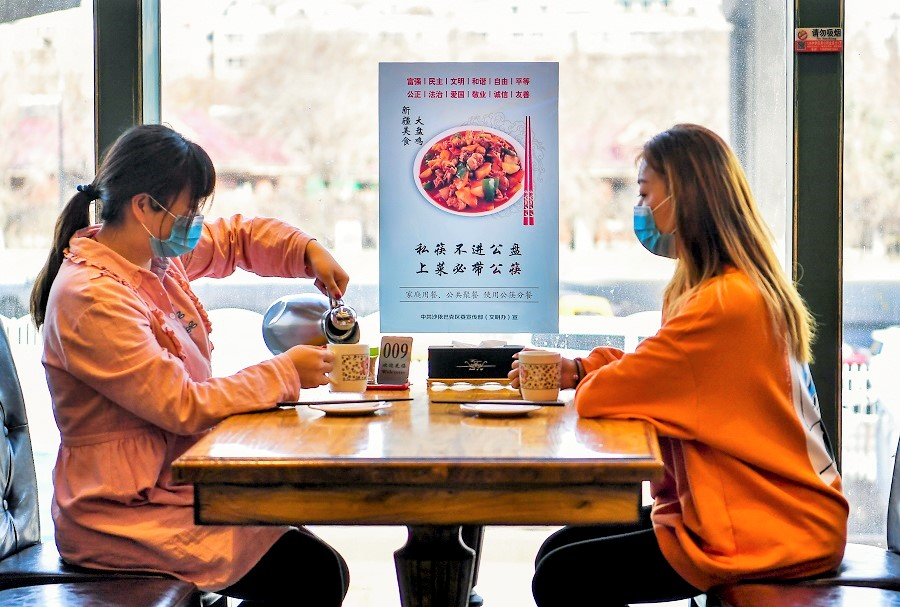 In this photo taken on 3 April, a poster encouraging people to use serving chopsticks and sit apart is seen as two diners wait for their food to be served in a restaurant in Saybag District, Ürümqi, Xinjiang, China. (CNS)