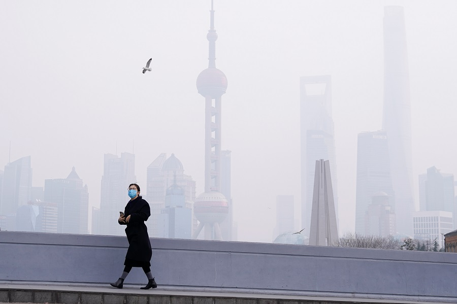 In this photo taken on 3 February 2020, a woman wearing a mask is seen on a bridge in front of the financial district of Pudong, Shanghai, China, as the country is hit by the Covid-19 pandemic. (Aly Song/Reuters)