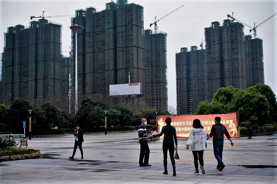 People with face masks are seen at a square near residential buildings under construction in Xianning, Hubei, China, on 25 March 2020. (Aly Song/Reuters)