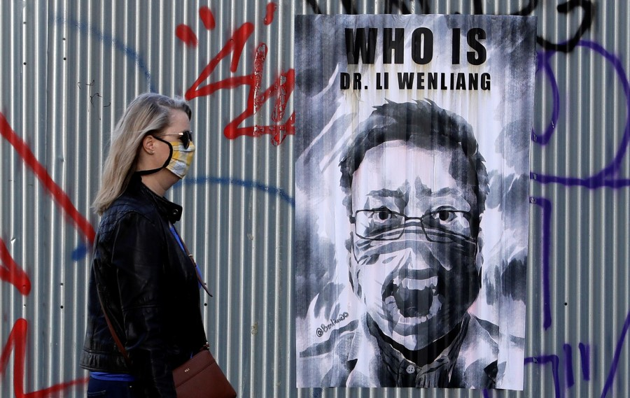 A woman in Prague walks past a poster of the late Li Wenliang, a Chinese ophthalmologist who tried to raise the alarm about COVID-19 and later died from it, March 27, 2020. (David W Cerny/REUTERS)