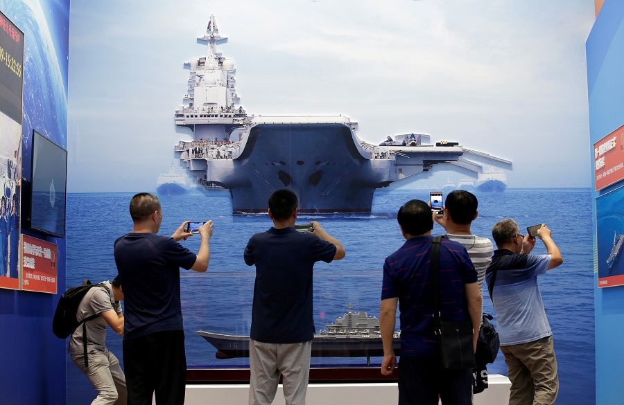In this file photo taken on 24 September 2019, visitors hold their mobile phones in front of exhibits showing the People's Liberation Army Navy's first aircraft carrier Liaoning, during an exhibition on China's achievements marking the 70th anniversary of the founding of the People's Republic of China at the Beijing Exhibition Center, in Beijing, China. (Jason Lee/File Photo/Reuters)