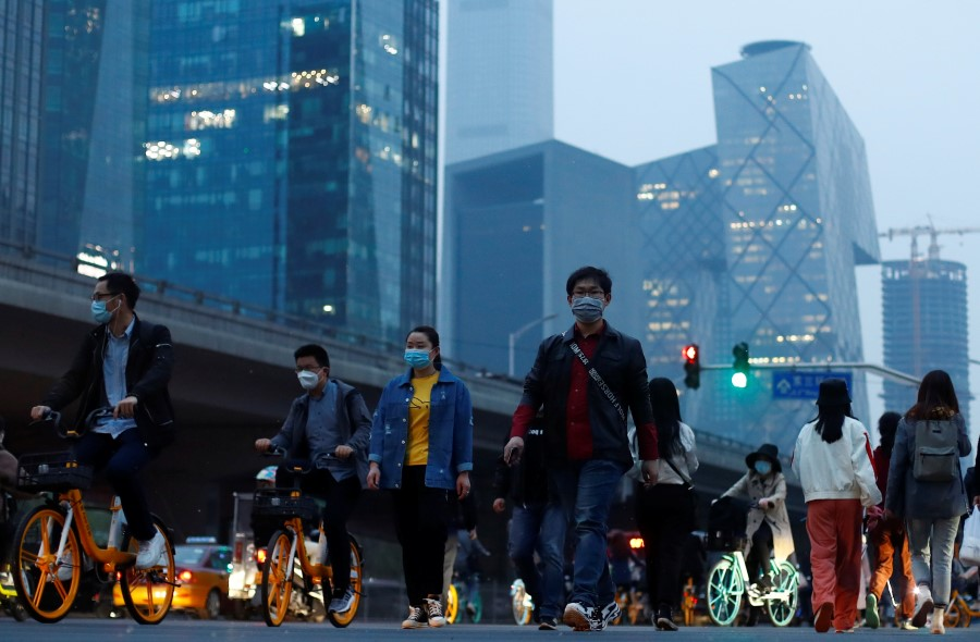 The skyline of the Beijing's Central Business District rises behind people crossing a street during evening rush hour, April 15, 2020.(Thomas Peter/REUTERS)