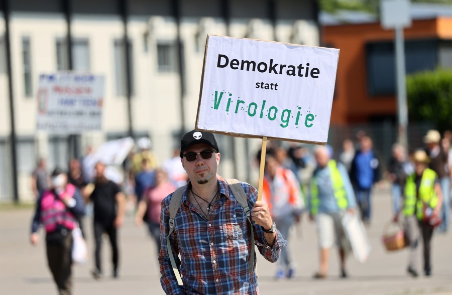 """A man holds up a sign reading """"democracy instead of virology"""" as he attends a protest against the government's restrictions following the coronavirus disease (COVID-19) outbreak, at Cannstatter Wasen area in Stuttgart, Germany, May 16, 2020. (Kai Pfaffenbach/REUTERS)"""
