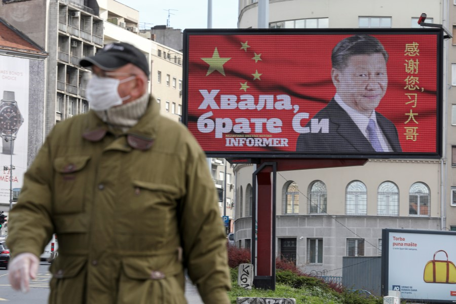 """A man wearing a protective mask passes by a billboard depicting Chinese President Xi Jinping as the spread of the coronavirus disease (COVID-19) continues in Belgrade, Serbia, 1 April 2020. The text on the billboard reads """"Thanks, brother Xi."""" (Djordje Kojadinovic/REUTERS)"""