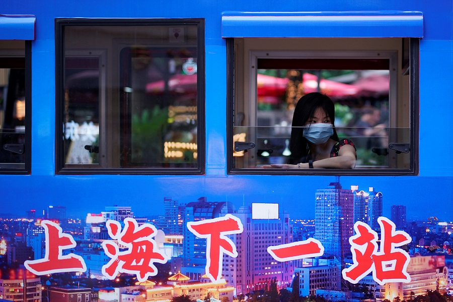 A woman wearing a face mask is seen on a tourist electric car at a shopping area in Shanghai, China, on 16 June 2020. (Aly Song/Reuters)