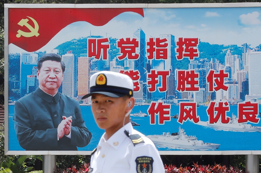 A People's Liberation Army (PLA) Navy soldier stands in front of a backdrop featuring Chinese President Xi Jinping during an open day of Stonecutters Island naval base, in Hong Kong, China, on 30 June 2019. (Tyrone Siu/File Photo/Reuters)