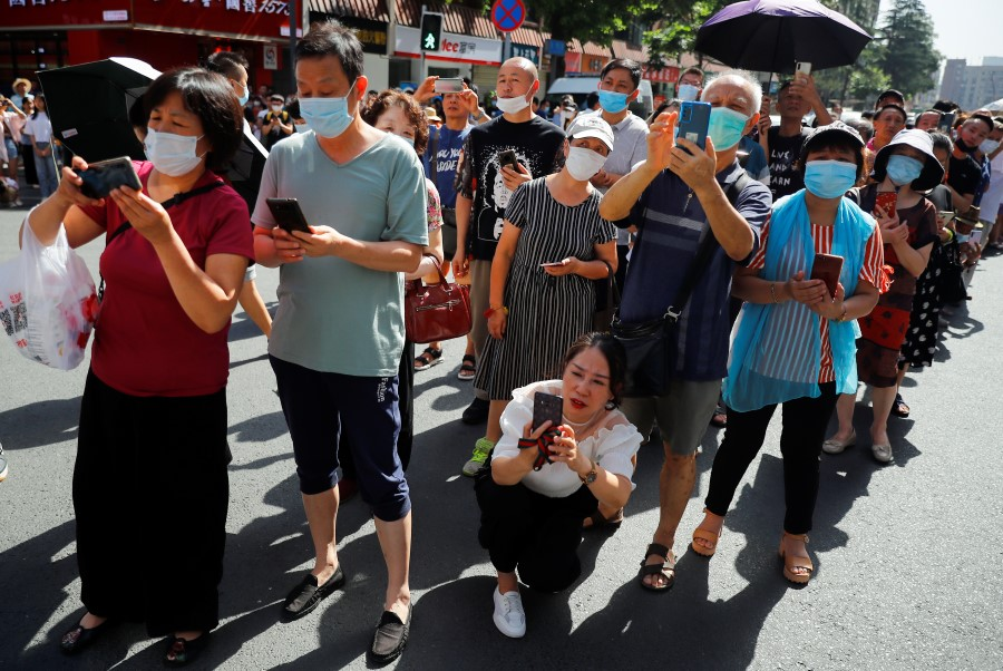 People gather near the US Consulate General in Chengdu, 27 July 2020, as the final group of U.S. personnel from the consulate is expected to leave after China ordered its closure in response to a US order for China to shut its consulate in Houston. (Thomas Peter/REUTERS)