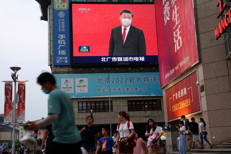People walk past a giant screen showing a news footage of Chinese President Xi Jinping wearing a face mask, at a shopping area in Beijing, 31 July 2020. (Tingshu Wang/REUTERS)