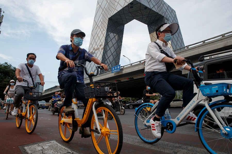 People ride shared bicycles past the CCTV headquarters in the Central Business District in Beijing, China, on 4 August 2020. (Thomas Peter/Reuters)