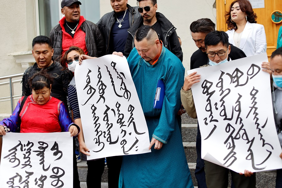 Demonstrators, holding signs with Mongolian script, protest against China's changes to school curriculums that remove Mongolian language from core subjects, outside the Mongolian Ministry of Foreign Affairs in Ulaanbaatar, Mongolia, 31 August 2020. (Anand Tumurtogoo/Reuters)