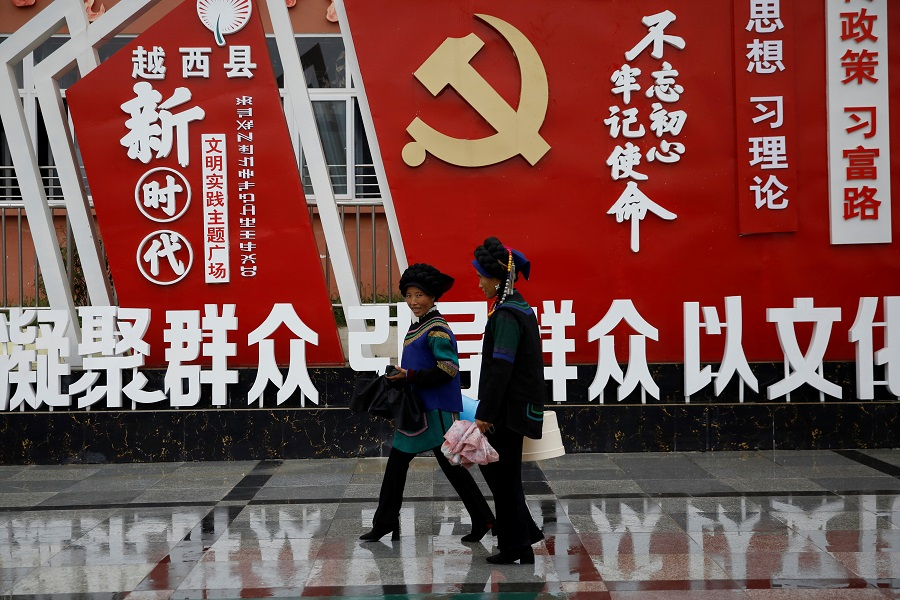 Ethnic Yi women walk past an installation featuring a logo of the Communist Party of China and numerous slogans at the Chengbei Gan'en Community, a residential complex built for a relocation programme as part of China's poverty alleviation effort, in Yuexi county, Liangshan Yi Autonomous Prefecture, Sichuan province, China, 11 September 2020. (Tingshu Wang/Reuters)