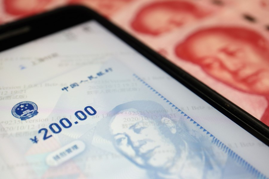 China's official app for digital yuan is seen on a mobile phone next to 100-yuan banknotes in this illustration picture taken 16 October 2020. (Florence Lo/REUTERS)