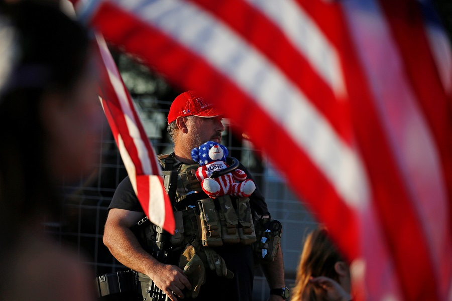 """A supporter of US President Donald Trump carries a teddy bear and a semi-automatic rifle at a """"Stop the Steal"""" protest after the 2020 US presidential election was called for Democratic candidate Joe Biden, at the Maricopa County Tabulation and Election Center (MCTEC), in Phoenix, Arizona, US, 9 November 2020. (Jim Urquhart/Reuters)"""