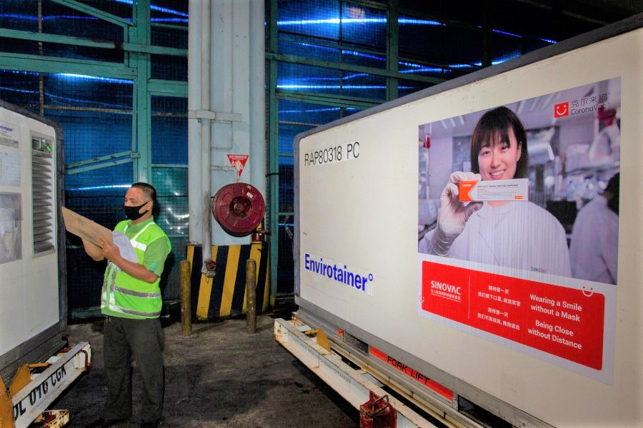 An officer checks a container with COVID-19 vaccines from China's Sinovac Biotech Ltd., as they arrive at Soekarno-Hatta International Airport in the first shipment to Indonesia, in Tangerang, near Jakarta, 6 December 2020. (Dhemas Reviyanto/Antara Foto via Reuters)