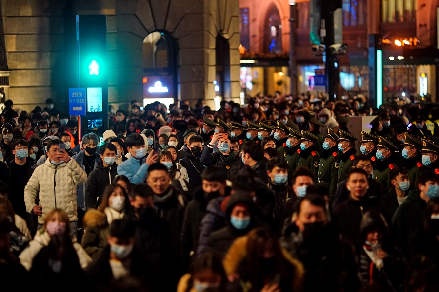 Paramilitary police stand guard as people gather to celebrate the arrival of the New Year near the Bund in Shanghai, China, 31 December 2020. (Aly Song/Reuters)