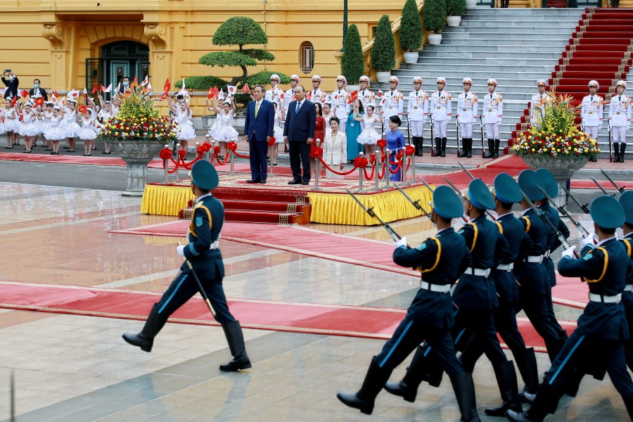 "The ""Yellow House"", Vietnam's Presidential Palace in Hanoi, is seen in the background during a visit by Japanese Prime Minister Yoshihide Suga (left) and his Vietnamese counterpart Nguyen Xuan Phuc (right) in Hanoi, Vietnam, 19 October 2020. (Minh Hoang/Pool via REUTERS)"