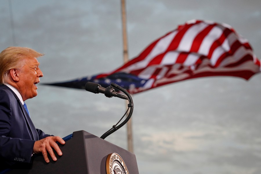 US President Donald Trump speaks, with a flag behind him, during a campaign rally at Cecil Airport in Jacksonville, Florida, US, 24 September 2020. (Tom Brenner/REUTERS)