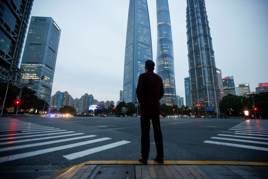 A man stands at a crossroads in Lujiazui financial district in Pudong, Shanghai, China, 5 March 2021. (Aly Song/Reuters)
