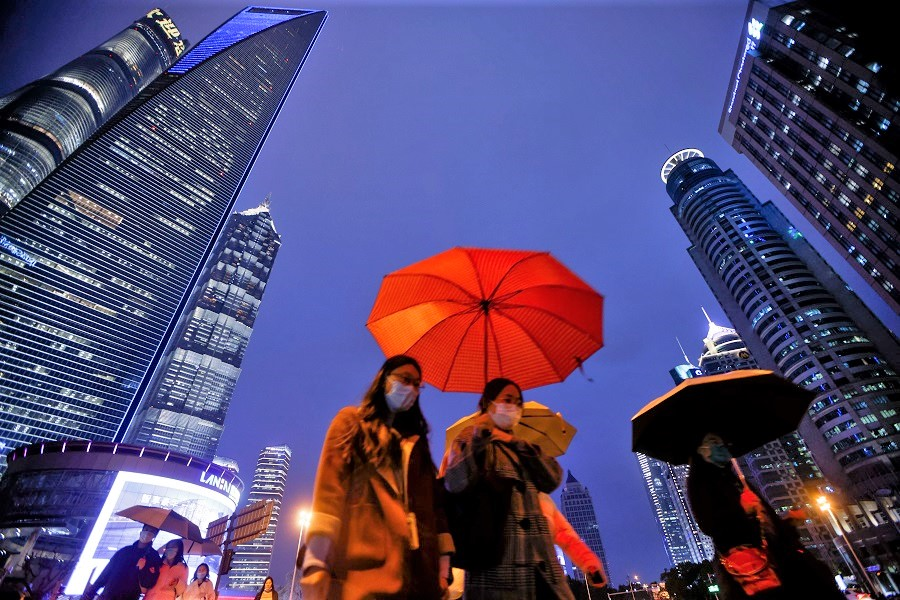 People walk with umbrellas in Lujiazui financial district in Pudong, Shanghai, on the day of the opening session of the National People's Congress (NPC), China, 5 March 2021. (Aly Song/Reuters)