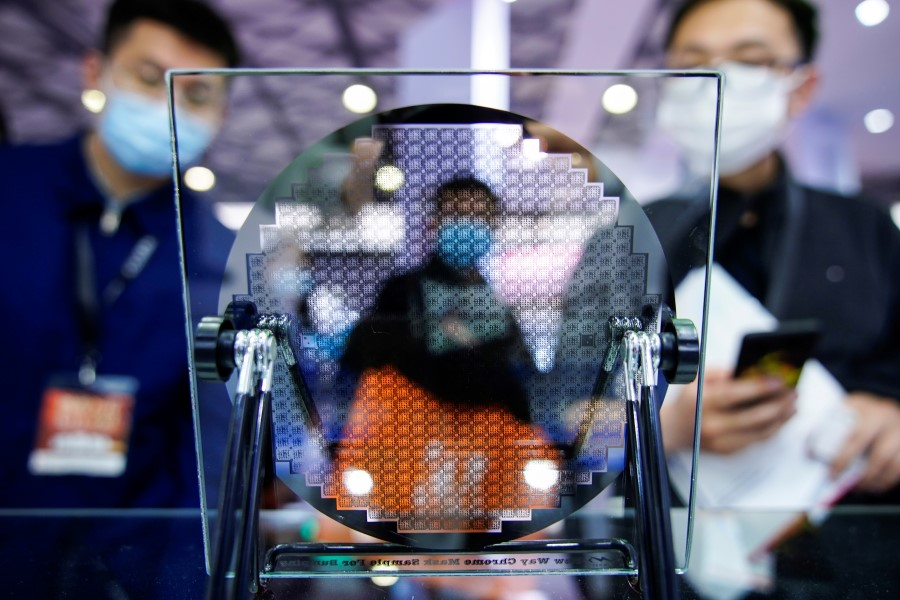 Visitors look at a display of a semiconductor device at Semicon China, a trade fair for semiconductor technology, in Shanghai, China, 17 March 2021. (Aly Song/Reuters)