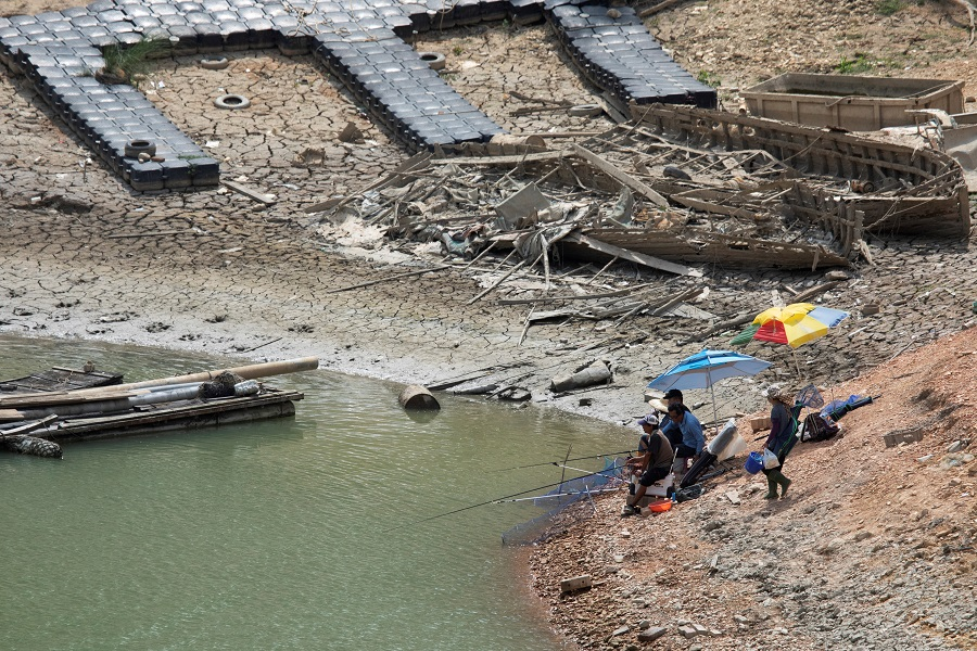 People fish at the Sun Moon Lake amid low water levels during an islandwide drought in Nantou, Taiwan on 15 May 2021. (Annabelle Chih/Reuters)