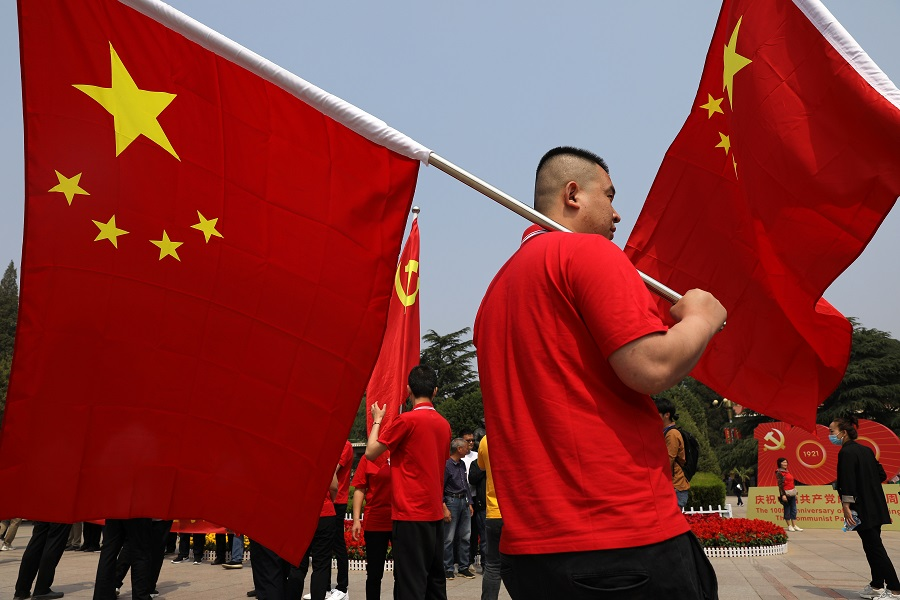 A visitor carries a Chinese national flag at Xibaipo Memorial Hall, ahead of the 100th founding anniversary of the Communist Party of China in Xibaipo, Hebei province, China, 12 May 2021. (Tingshu Wang/Reuters)