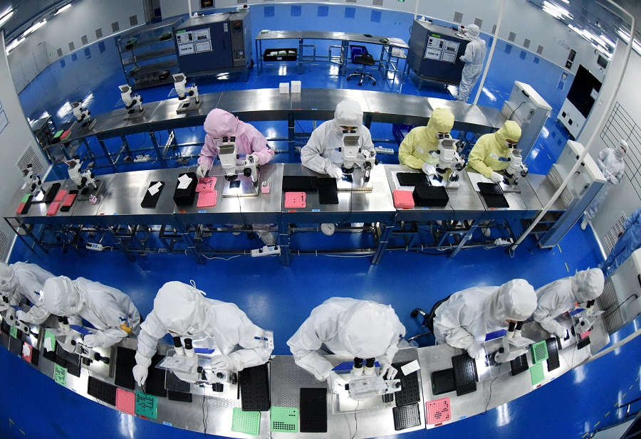 Employees work on a production line manufacturing camera lenses for mobile phones at a factory in Lianyungang, Jiangsu province, China, 30 April 2019. (China Daily via Reuters)