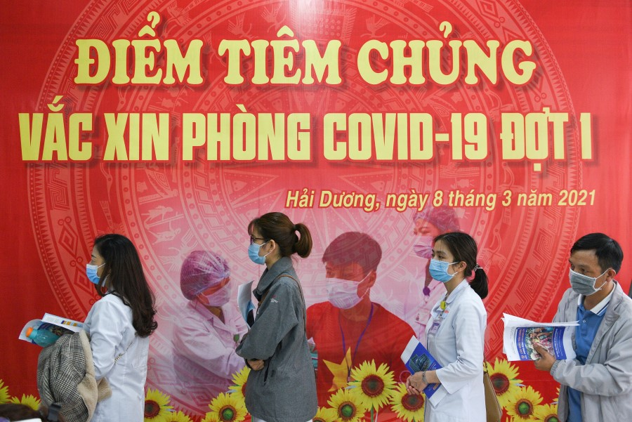 Health workers wait for their turn as Vietnam starts its official rollout of AstraZeneca's Covid-19 vaccine for health workers, at Hai Duong Hospital for Tropical Diseases, Hai Duong province, Vietnam, 8 March 2021. (Thanh Hue/Reuters)