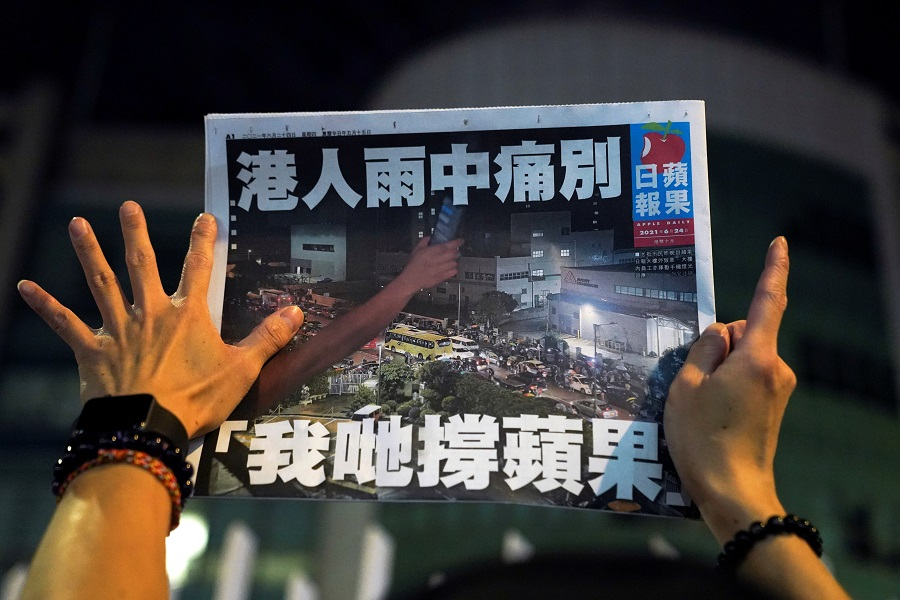 A supporter gestures while holding the final edition of Apple Daily in Hong Kong, China, 24 June 2021. (Lam Yik/Reuters)