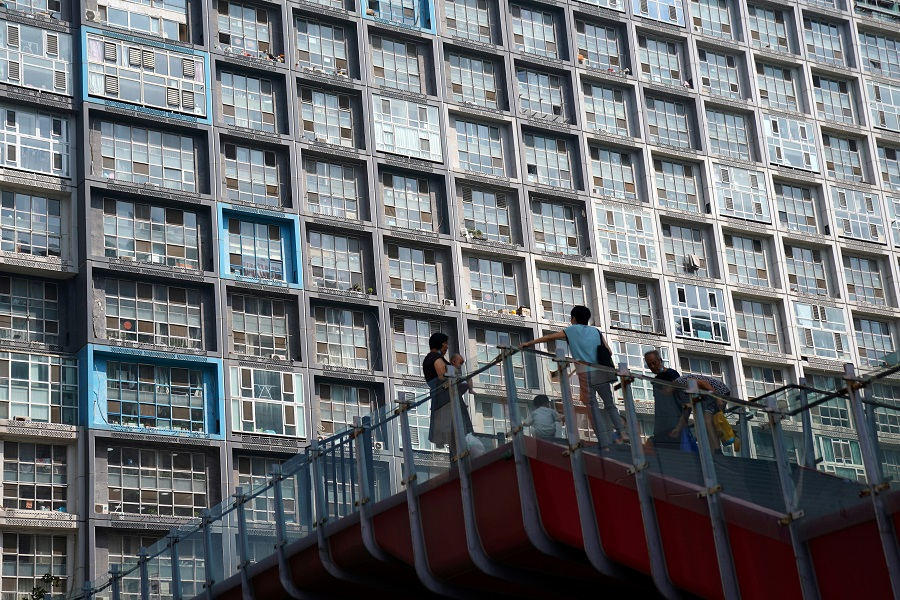 People wearing face masks are seen on an overpass in front of a residential building in Beijing, China, 11 August  2020. (Tingshu Wang/File Photo/Reuters)