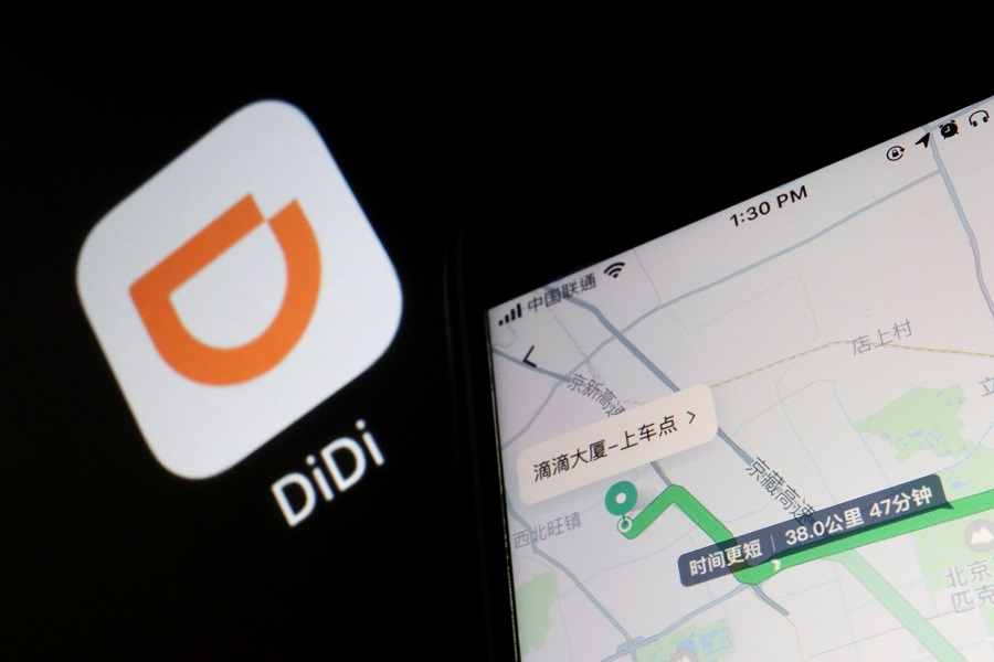 A navigation map on the app of Chinese ride-hailing giant Didi is seen on a mobile phone in front of the app logo displayed in this illustration picture taken 1 July 2021. (Florence Lo/Illustration/File Photo/Reuters)