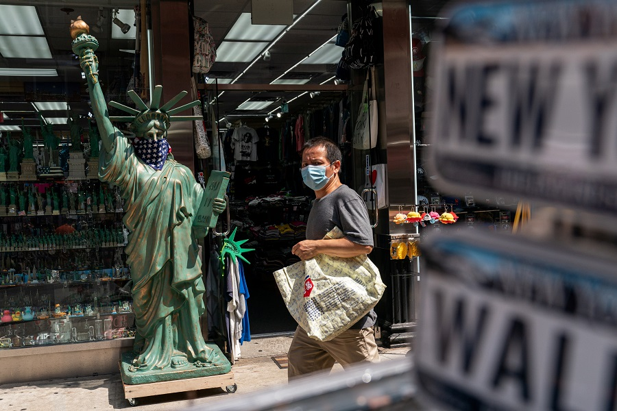 A man wearing a mask walks past a model of the Statue of Liberty at a tourist store in New York City, US, 18 July 2021. (Jeenah Moon/Reuters)