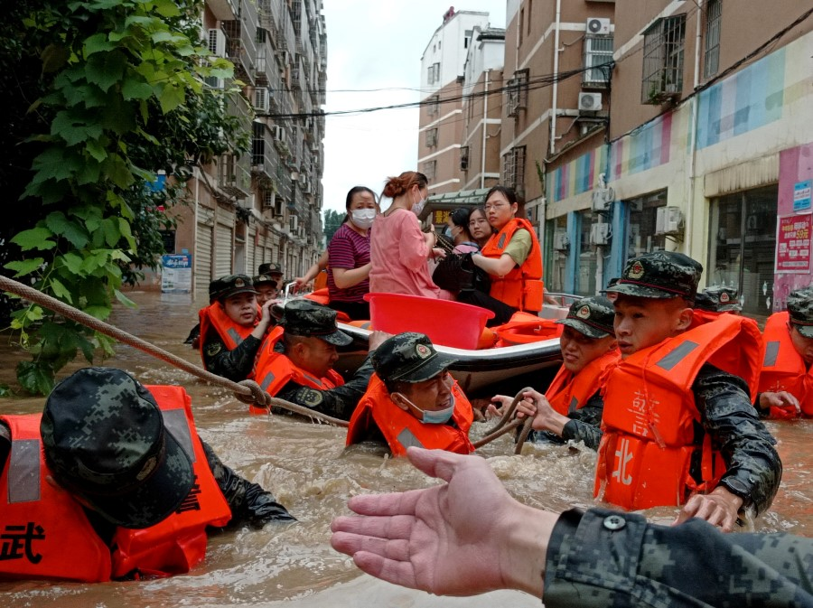 Paramilitary police officers evacuate residents stranded by floodwaters with a boat following heavy rainfall in Hedian town of Suizhou, Hubei province, China, 12 August 2021. (cnsphoto via Reuters)