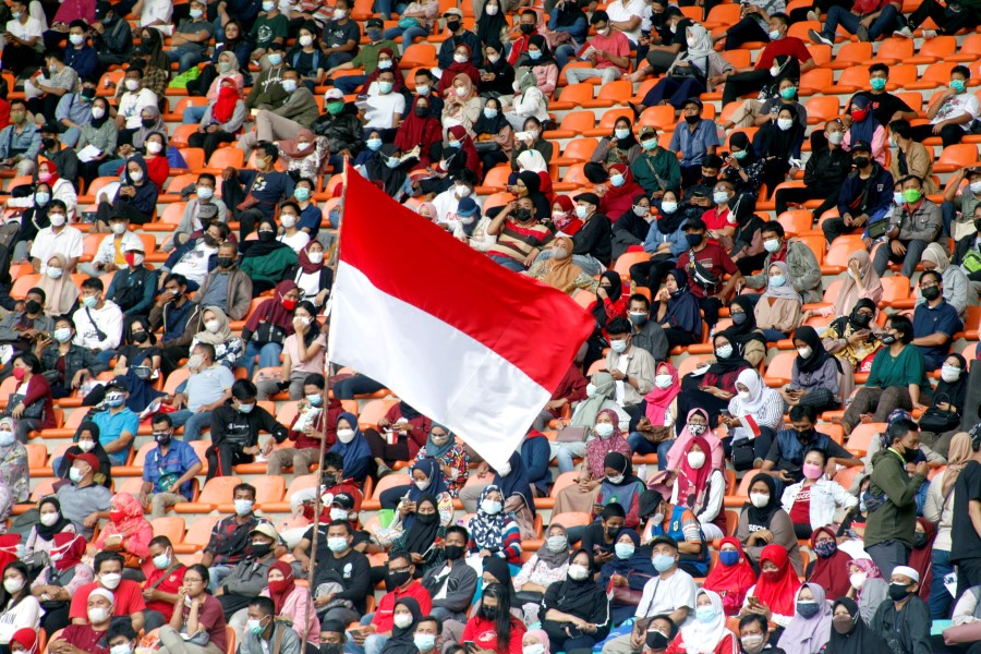 The Indonesian flag flies as people wearing protective face coverings wait to receive a coronavirus disease (COVID-19) vaccine dose at Pakansari Stadium in Bogor, on the outskirts of Jakarta, Indonesia, 14 August 2021. (Yulius Satria Wijaya via Reuters)