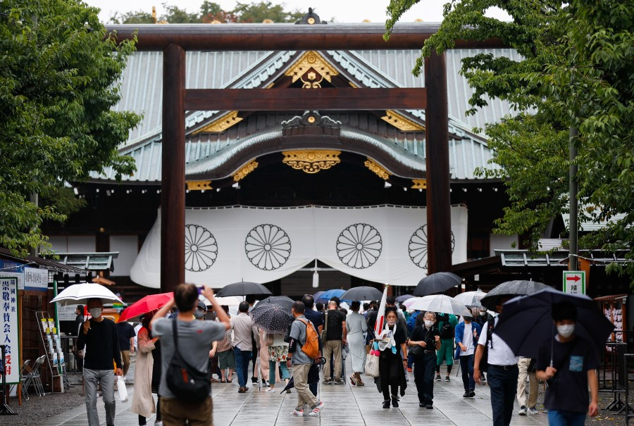 People carry umbrellas as they visit Yasukuni Shrine in Tokyo, Japan, 15 August 2021. (Issei Kato/Reuters)