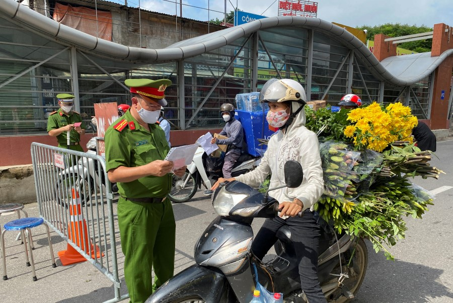 Vietnam police officers inspect authorised travel documents of commuters at a checkpoint during the first day of the extended lockdown in Hanoi, Vietnam, 6 September 2021. (Stringer/Reuters)