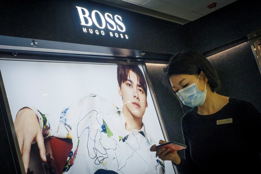 A woman walks past a store of German fashion house Hugo Boss in Beijing, China, 27 March 2021. (Thomas Peter/File Photo/Reuters)
