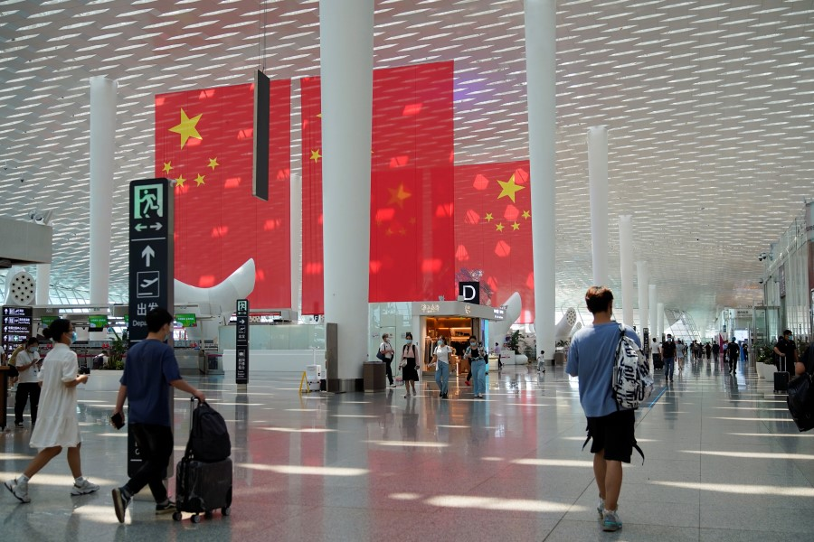 Travellers walk past Chinese flags ahead of China's National Day and Golden Week holiday, at Shenzhen Baoan International Airport in Shenzhen, Guangdong province, China 30 September 2021. (Aly Song/Reuters)