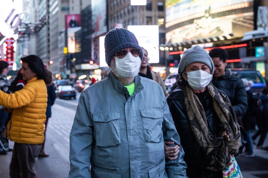 Pedestrians wear protective masks while walking in New York, 7 March 2020. The availability of testing in the US lags far behind the needs of public health workers on the front lines. (Jeenah Moon/Bloomberg)
