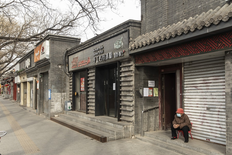 An elderly person wearing a protective masks sits in front of shuttered stores near a hutong neighborhood in Beijing, China, on 18 March 2020. (Qilai Shen/Bloomberg)