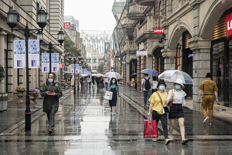 Pedestrians wearing protective masks walk with umbrellas past stores in Wuhan, China, on 30 April 2020. (Qilai Shen/Bloomberg)