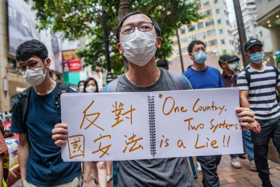 """A demonstrator holds a sign reading """"One Country, Two Systems is a Lie"""" as he marches through the Causeway Bay district during a protest in Hong Kong, 27 May 2020. (Lam Yik/Bloomberg)"""