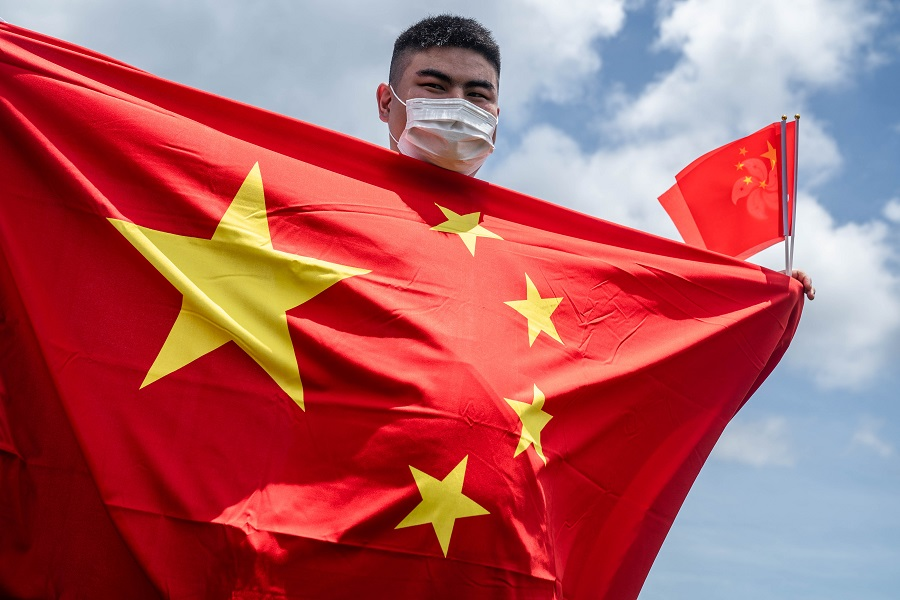 A government supporter wearing a protective mask holds Chinese and Hong Kong Special Administrative Region (HKSAR) flags to celebrate the passage of a national security law in Hong Kong, China, on 30 June 2020. (Lam Yik/Bloomberg)