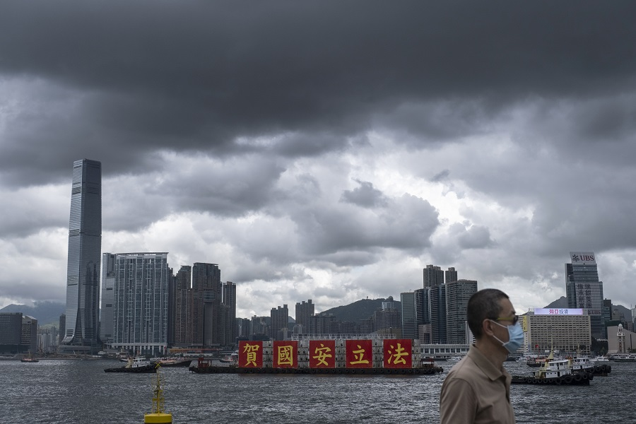 A man wearing a protective mask walks by the waterfront as a barge sails past with a message celebrating the passage of the new national security law in Hong Kong, China, 1 July 2020. (Roy Liu/Bloomberg)