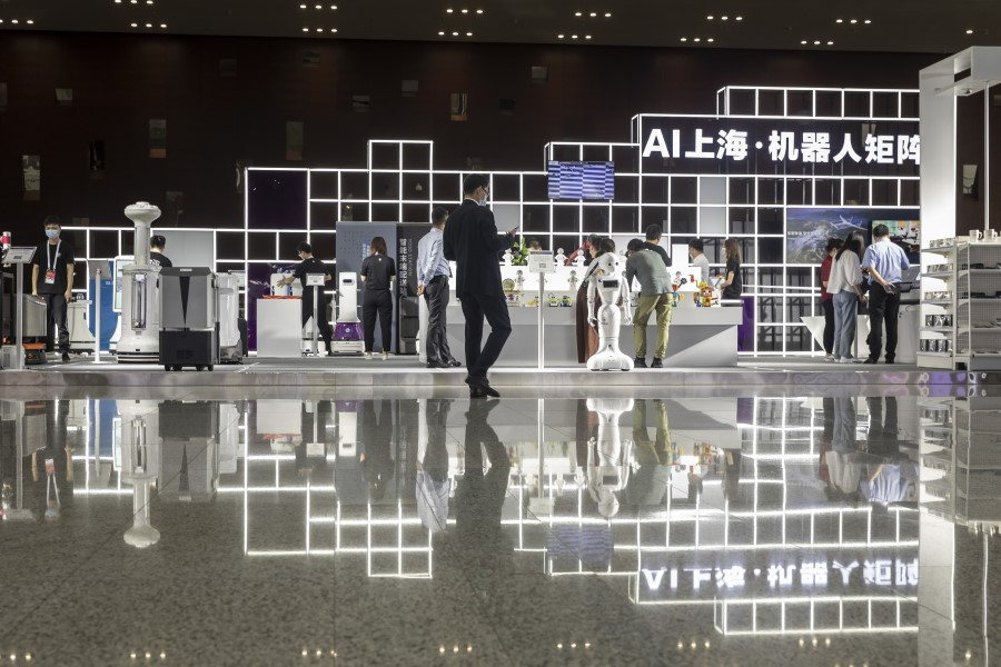 Attendees browse as a humanoid robot stands in the exhibition display area at the World AI Conference in Shanghai, 9 July 2020. (Qilai Shen/Bloomberg)