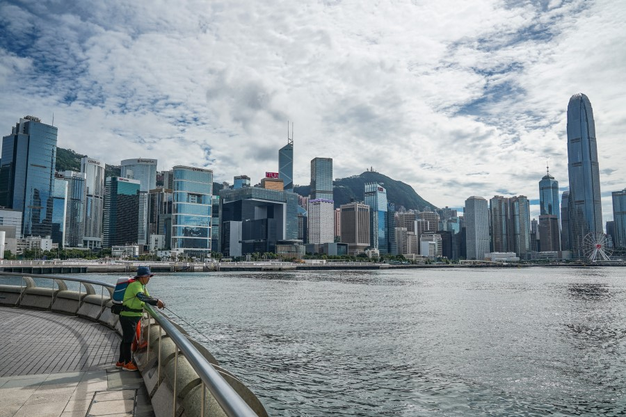 An angler fishes as buildings stand across the Victoria Harbor in Hong Kong, China, 15 July 2020. (Lam Yik/Bloomberg)