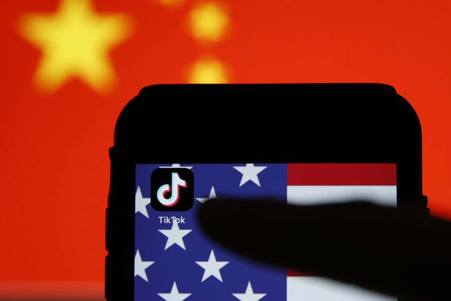 The TikTok app icon sits displayed on a smartphone in front of the national flags of China and the US in this arranged photograph in London, 3 August 2020. (Hollie Adams/Bloomberg)