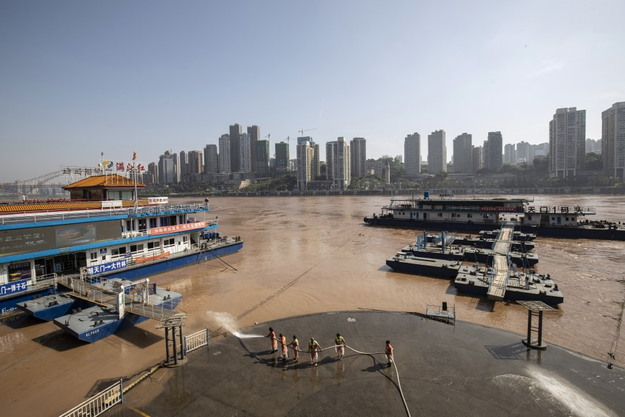 Workers use a fire hose to wash away mud left by receded floodwaters off the Chaotianmen docks in Chongqing, 28 July 2020. (Qilai Shen/Bloomberg)