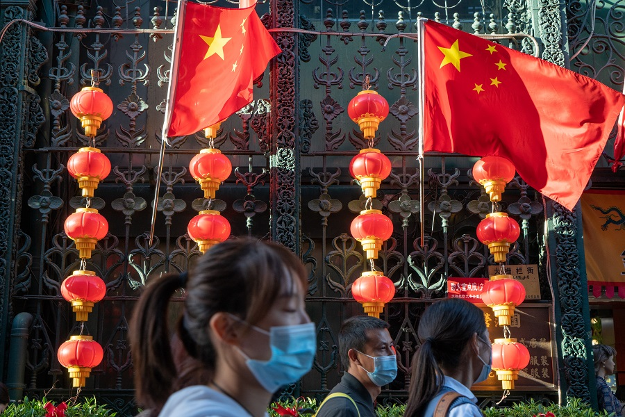 Visitors wearing protective masks walk by Chinese national flags and red lanterns decorated to celebrate the National Day in Beijing, China, 4 October 2020. (Yan Cong/Bloomberg)